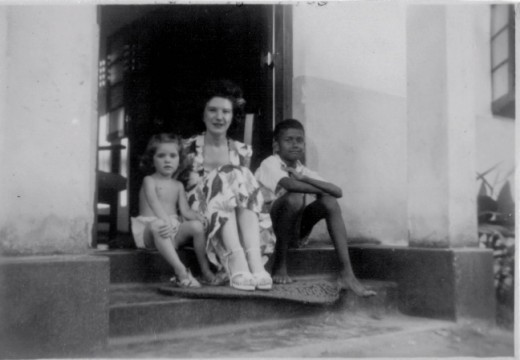 Mum and me sitting on the doorstep of our bungalow with a neighbour.