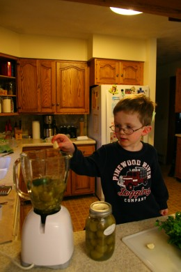 My four year old son adds garlic to the blender.