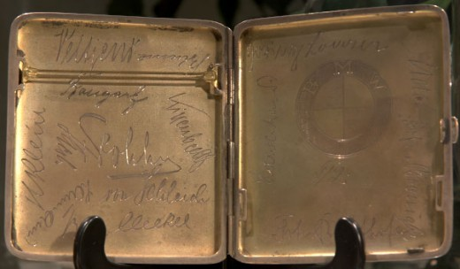 "Cigarette case signed by German aces, on display at the Vintage Aero Flying Museum.  At the bottom of the right half, behind the leg of the holder, you can make out ""Richthofen""."
