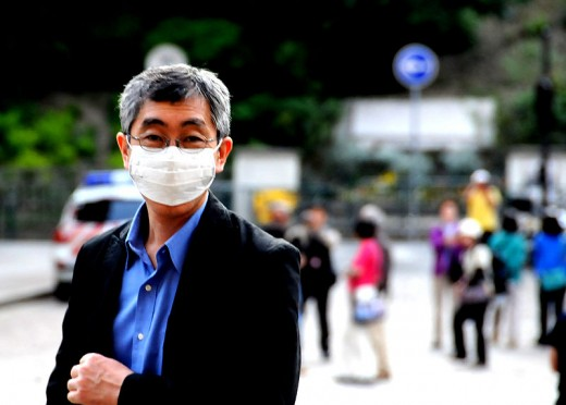 Man wearing a face mask to prevent catching the swine flu.