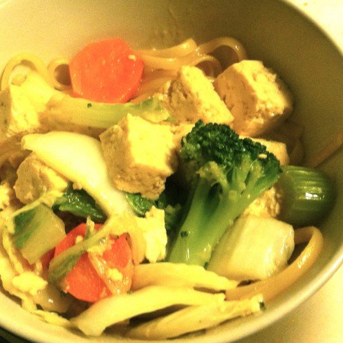 Steamed tofu served with stir-fried vegetables and rice noodles.