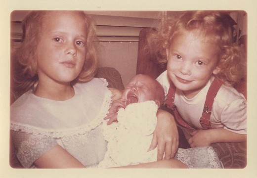 Me as a baby held by my older sister with my older brother looking on