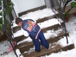 child clears snow from steps