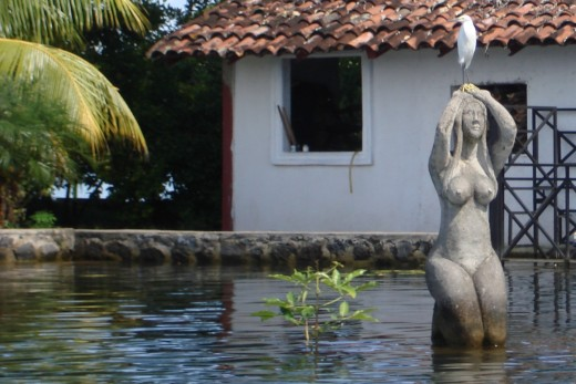 A well-place statue, very artsy, especially with an egret perched on top.