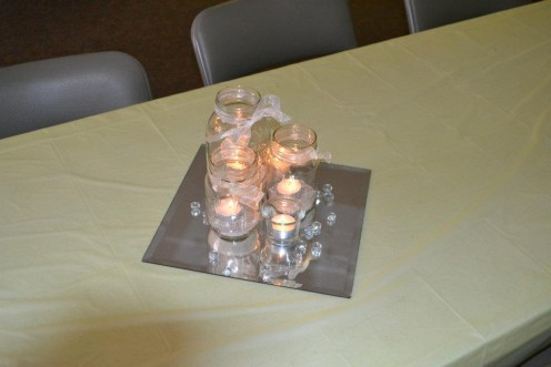 These simple centerpieces incorporate mason jars, candles, sand, mirror tiles and a few clear marbles and make an elegant but inexpensive decoration.