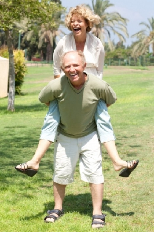 senior citizen giving wife a piggyback ride