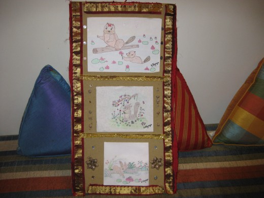 My artwork wall hanging is decorated with golden fabric strips, earrings, seashells and mirror-like papers.