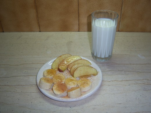 A glass of cold milk with a plate of chopped apple and banana drizzled with honey and sprinkled with cinnamon....