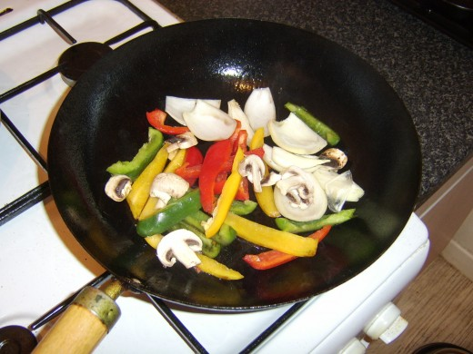 Vegetables are added to a smoking hot wok
