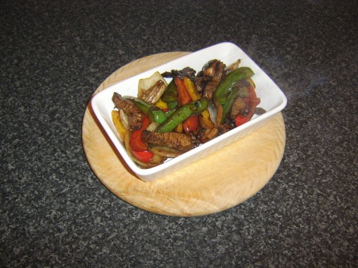 Stir fried steak and vegetables are added to a preheated serving dish