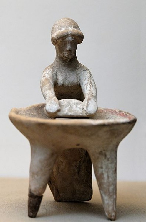 Woman grinding weat in a basin. Terracotta, Greek artwork, ca. 450 BC. From Kameiros, Rhodes