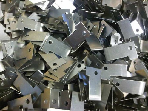 Spring stainless steel angle brackets used to hold lighting reflectors in place.  These parts have been produced from spring stainless steel coil, cut to size and then produced with simple fly press tooling.