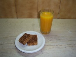 Chewy honey, oat and coconut flapjacks with a glass of fresh orange juice....