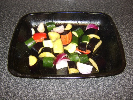 Olive oil and seasoning is added to the vegetables in a roasting tray