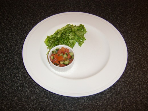 Shredded lettuce and salsa are plated in readiness