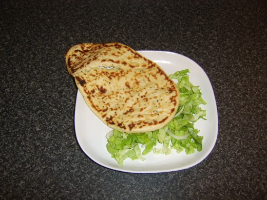 Naan bread and shredded salad are arranged on a plate