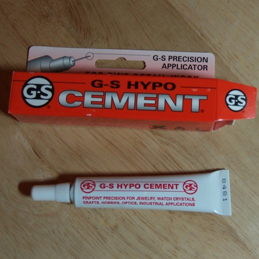 G-S Hypo Cement has a precision applicator which makes it very easy to glue the end of the memory wire into the hole of the half-drilled bead end..