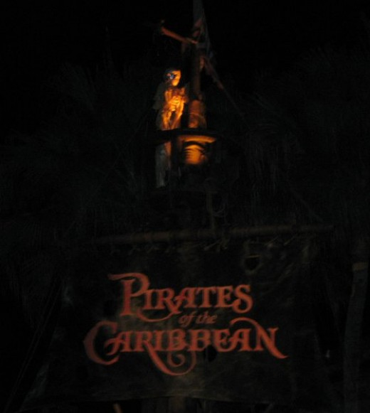 Entrance to Pirates of the Carribean, lit up at night.