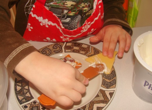 Alex carefully spreads the cream cheese onto the cheese slice.