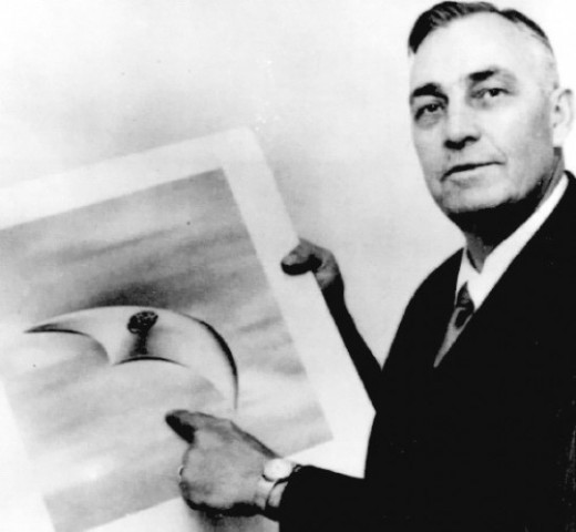 Kenneth Arnold with artist's rendering of of the crescent shaped UFO he saw in 1947.