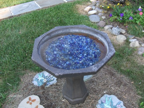 Water garden blue round glass to draw birds and decorative stepping stones around the bath.