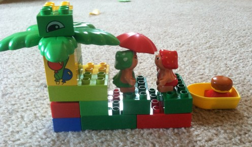 "LEGO Creation: A ""house"" for the girl holding the umbrella had to contain a boat (far right), several ""guests"", five green blocks and three yellow blocks."