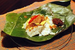 Indonesian Nasi uduk (rice cooked in coconut milk) comes wrapped in banana leaf and featured fried tempeh (soya bean cake), omelet, seasoned and roasted coconut flakes), and peanuts.