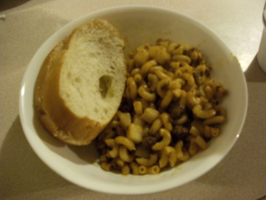 A Serving of Chili 'n' Pasta Hash with French bread dipped in homemade Garlic butter.
