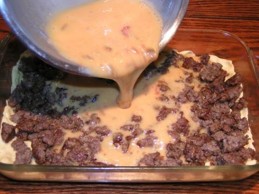 Pour egg mixture over dough and sausage.