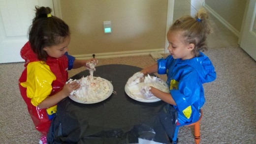 Shaving cream for all! The table has been covered with a trash bag and the kids have been covered with raincoats instead of smocks.