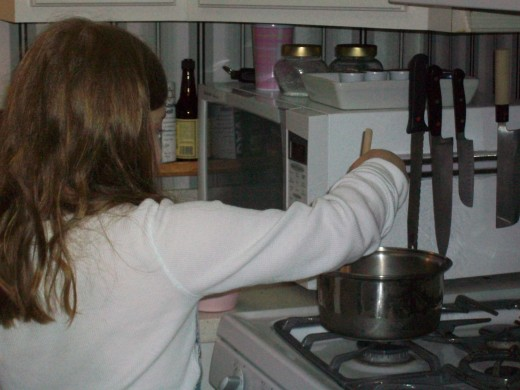 A child who is tall enough can stir the pudding on the stove under close supervision.
