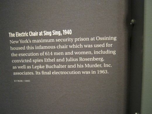 The plaque explaining the electric chair, which perhaps would be better displayed in a more prominent place rather than behind the chair, off to one side.