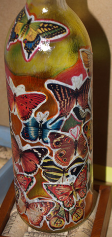Detail of completed wine bottle project. Note the use of the stained glass marking pens in the open spaces between the glued images.