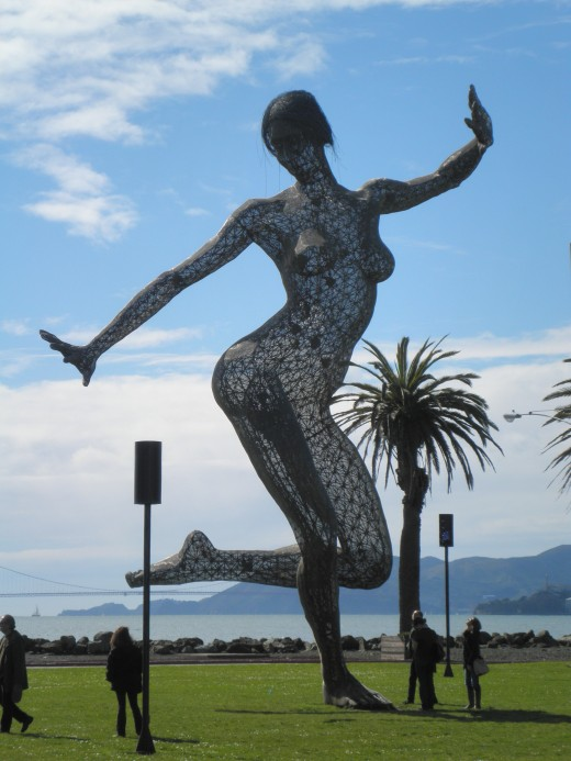 "I took this photo in March 2012 of ""Bliss Dance"". If you look closely you can see the Golden Gate Bridge in the distance. For further interest, look at the size of the people below the sculpture! It really gives you a good idea of how large she is!"