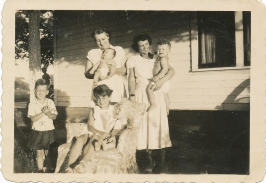 Picture of my grandmother, Wilma, on right holding her son, my mom in the foreground with brown hair, and my great grandmother beside Wilma.
