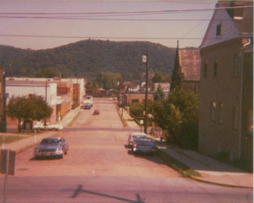 Early 1980s view looking north on Broadway Street, from the grounds of the Corapolis Library. Just visible is a P&LE U28B locomotive heading eastbound towards Pittsburgh. The buildings at Broadway & 5th Avenue have been replaced by a Rite-Aid.
