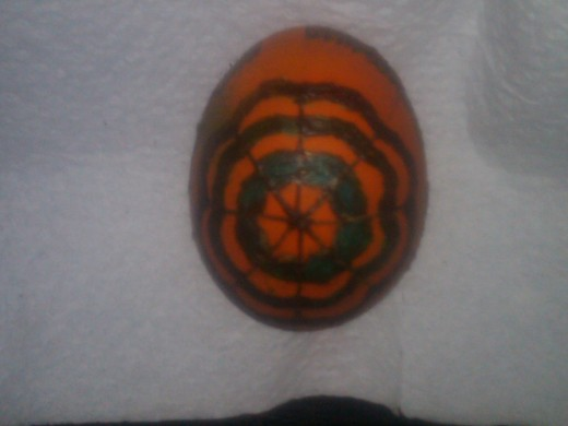 Orange egg with blue outlines covered in wax
