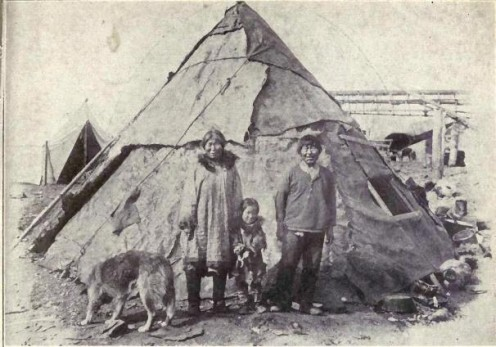 An Inuit family with their Alaskan Malamute in 1915.