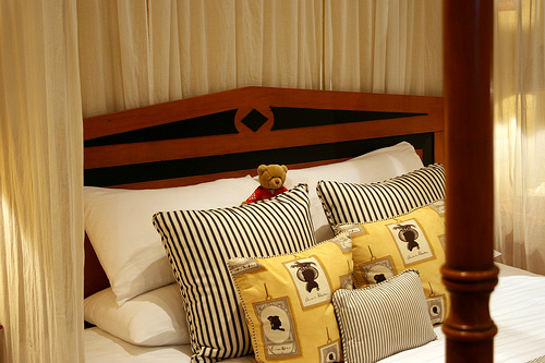 A lovely arrangement of pillows against a stately headboard makes a simple guest room look like the royal suite.
