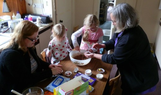 Granny helps the kids fill the paper cases with the chocolate mixture