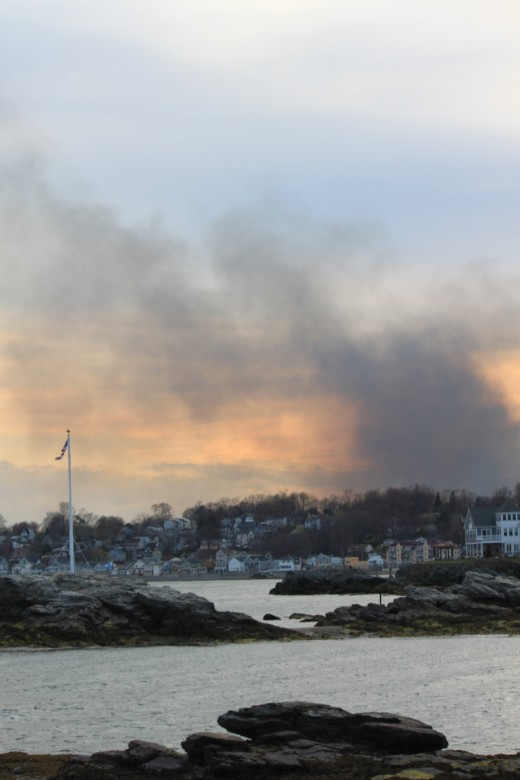 smoke starts to mix with sunset along the beach