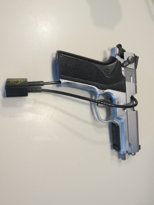 Side view of cable locked handgun.