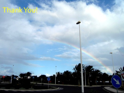 Rainbow over Canaries - I loved the way the rainbow ended in the road sign pointing down as if to the pot of gold!   © Mohan Kumar 2012