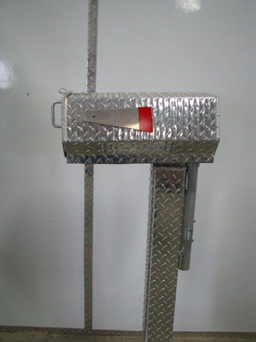 Heavy duty vandal and snow plow resistant mail box with swing arm and post protector.