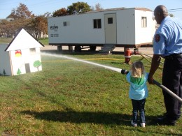 Grace practices putting out a house fire with a real fire hose.