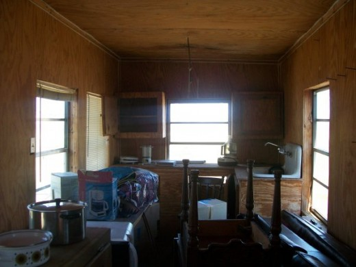 This is the interior of my little house before  did anything to it. As you can see it is completely unpainted and was being used as a storage space by the owners. I painted the walls, cabinets and ceiling, installed light fixtures.