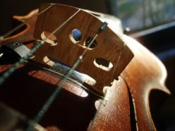 Why does a violin string change its note as a finger is moved up or down it?