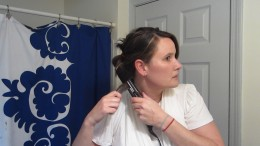 """Wrap the hair around the flat iron.  Hold onto the end or """"tail"""" and pull the hair through."""