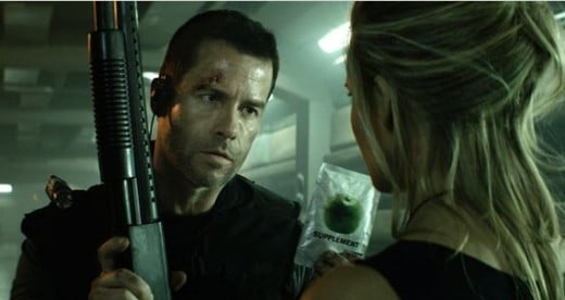 Guy Pearce offers Maggie Grace a concentrated apple in this scene from the science fiction movie Lockout.