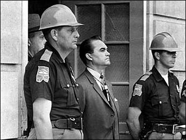 Alabama Governor George Wallace, a Democrat, stands at the door of Foster Auditorium at the University of Alabama in an attempt to prohibit two black students, Vivian Malone and James Hood, from attending college at that school.